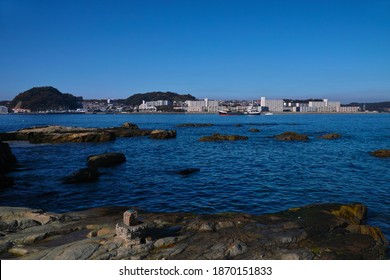 YOKOSUKA CITY, KANAGAWA PREFECTURE, JAPAN - DECEMBER 7th, 2020: A Sunny View of the Mouth of Uraga Bay, with a Sand Carrier Entering into the Bay