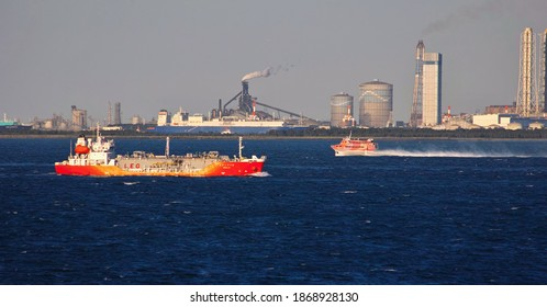 YOKOSUKA, KANAGAWA, JAPAN - NOVEMBER 21st, 2020: An LEG Carrier and a Jetfoil Sailing through the Uraga Channel in Tokyo Bay; a View of Tokyo-bay Traffic, with Thermal Power Plants in the Background