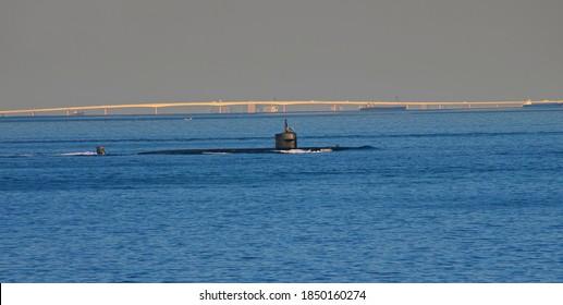 "YOKOSUKA, KANAGAWA / JAPAN - NOVEMBER 5th, 2020: USS Providence (SSN-719), a Los Angeles-class Submarine, Navigating Tokyo Bay toward the Pacific; the ""Tokyo-wan Akua-rain"" Sea Bridge Shining Far Away"