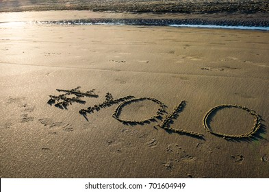#YOLO (hashtag) written in the sand on the beach at sunset. You Only Live Once slang