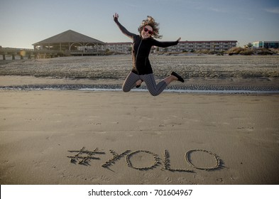 #YOLO (hashtag) written in the sand on the beach and an adult female jumping. You Only Live Once slang