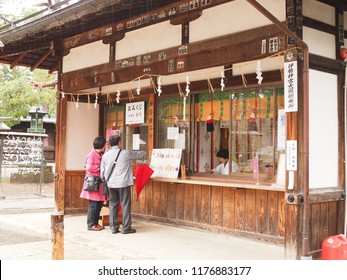 Yonezawa, Yamagata, Japan. April 18, 2018. A couple are visiting Japanese Shinto-shrine. They are choosing some Omamori,Japanese amulets. the woman who in the shop is Miko, Shrine maiden or priestess.