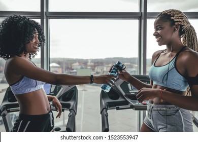 Yong african beautiful woman giving bottle her friend on break after training. Two attractive black girls drinking water on treadmill after activity. Weightloss calories burn