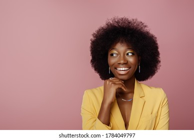 Yong beautiful happy smiling African American woman, model wearing elegant jewelry, yellow blazer, posing in studio, on pink background. Copy, empty space for text