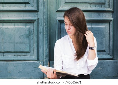 Yong beautiful woman reading a book. Green door background