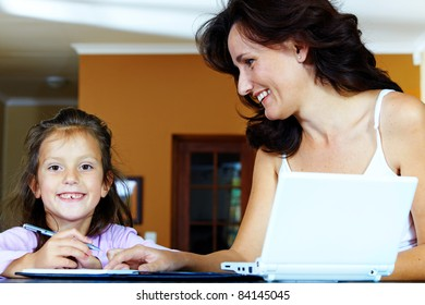 Yong brunette mother in her thirties helping her daughter with  homework while sitting at home behind computer