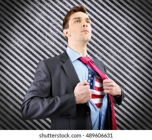 Yong businessman showing USA flag under suit on pattern background.