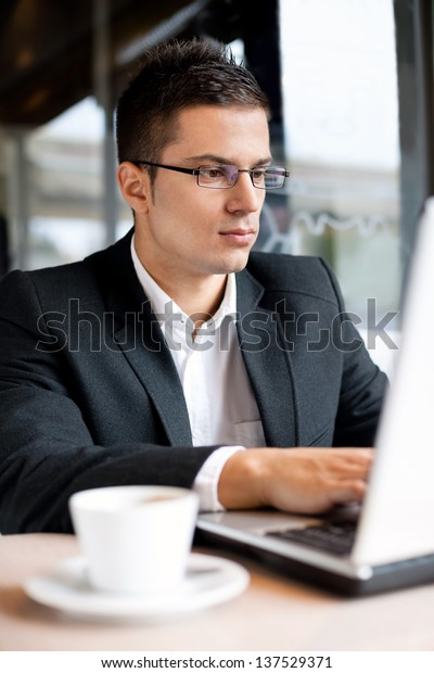 Yong businessman working on laptop in cafe