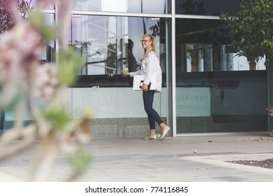 yong female entering the office holding a laptop. Employee enters the building. Glass door, city,urban.