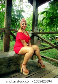 Yong female model with turban and red clothing sitting on wooden bench in park