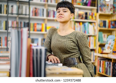 Yong female seller, student, business owner, standing amid books