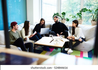 Yong freelance crew working hard on finding creative solution for internet social media tasks, sitting in coworking space using modern technology and consulting with skilled professional leader