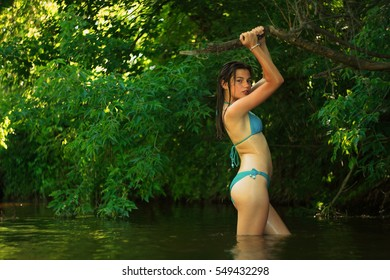 Yong happy girl relaxing in the forest river in summer time. Looked in camera