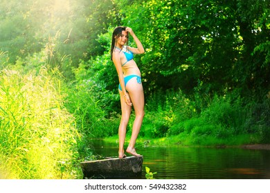 Yong happy girl relaxing in the forest river in summer time