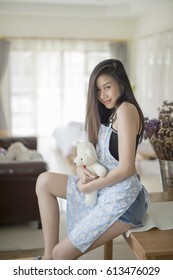 Yong happy girl with Teddy Bear with Apron sitting in kitchen room in the morning.