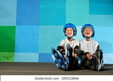 Yong little athletic boys on roller sitting against the blue graffiti wall. Rollerblading child