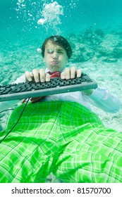 Yong man in formal clothes working with keyboard underwater