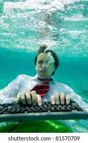 Yong man in formal clothes working with keyboard underwater with intense face expression