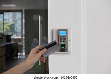 Yong man or woman use key card for access electronic door  control machine. Holding key card to access the door security systems. Selective focus