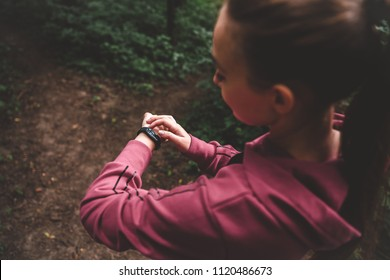 Yong woman athlete adjusts the smart watch before her run outdoors. Cropped top view of a sporty girl setting fitness bracelet on training. Smart watch health, heart rate and calories burn monitoring