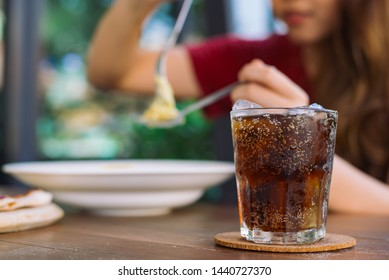 Yong woman with glass of refreshing cola at restaurant, Cola in glass with ice on green and bokeh nature background.