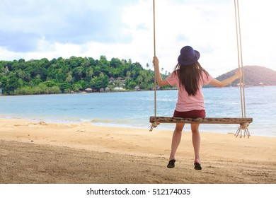 Yong woman playing rope swing on the beach