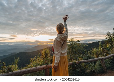 Yong woman watching Sunset in the Mountains at Doi Pui Viewpoint Doi Suthep-Pui National Park Chiang Mai Northern Thailand.
