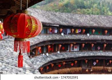 Yongding, Fujian Province / China - Dec 4, 2015: View along the wooden gallery and roof tiles of a Fujian Tulou. (福建土楼). An UNESCO World Heritage since 2008. Red, chinese lantern in the foreground.
