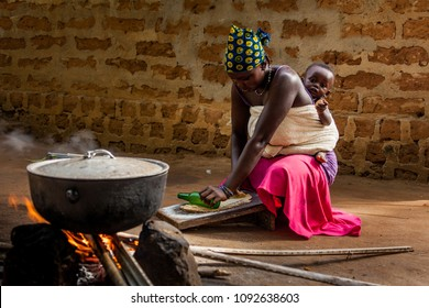 Yongoro, Sierra Leone - June 03, 2013: West Africa, unknown woman and child cooking in the village in front of the capital Freetown, SIerra Leone