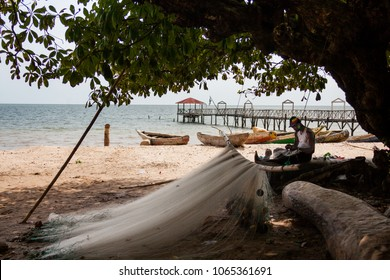YONGORO, SIERRA LEONE - June 05, 2013: West Africa, unknown person works and repairs fishing nets at the beach with fishing boats in front of the capital Freetown, Sierra Leone