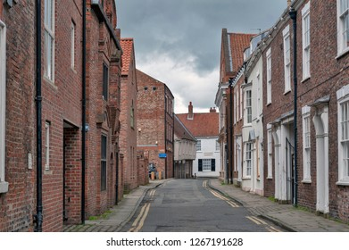 York, England - April 2018: Old brick buildings along Ogleforth Street towards Chapter House Street in historic district of City of York, England, UK