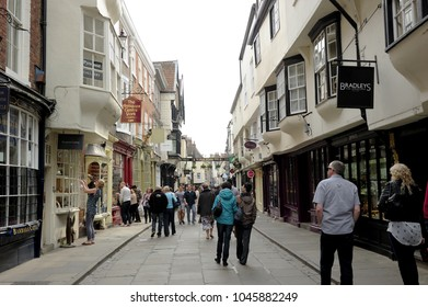 YORK, ENGLAND-5 MAY 2014: People walk in Stonegate, the cobbled shopping precinct that leads you up to the Minster one of the most attractive and architecturally varied streets in York, England, UK