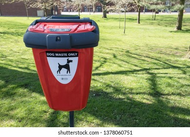 York / Great Britain - March 29, 2019 : Red Dog Waste poo poor bin trash can on green grass with logo