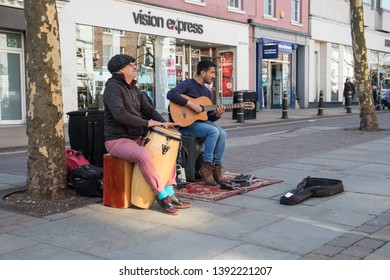 York / Great Britain - March 29, 2019 : Street performers busking playing music on the street with drum and guitar