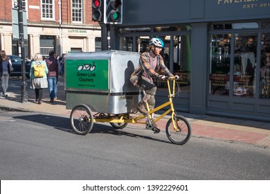 York / Great Britain - March 29, 2019 : Green Link Couriers cyclist on tricycle riding on street to make deliveries.