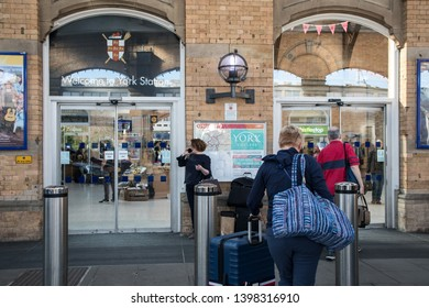 York / Great Britain - March 29, 2019 : Peple at the entrance exit to Yok Railways station with luggage for a journey