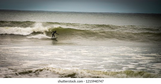 York, Maine USA: October 28th 2018: A surfer rides a storm wave following a Nor'easter storm.
