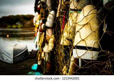 York, Maine USA: October 28th 2018: Fishing nets and buoys hang from the side of a wooden fishing shack with a dory boat lying upside down on the pier.