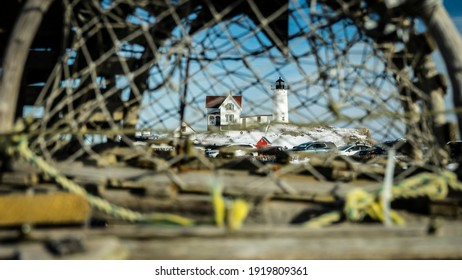 York, Maine, USA-February 13, 2021: A narrow focused shot looking through a lobster trap's netting reveling the Nubble Lighthouse in the background.