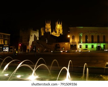 York night scene with spotlit Minster in far background.
