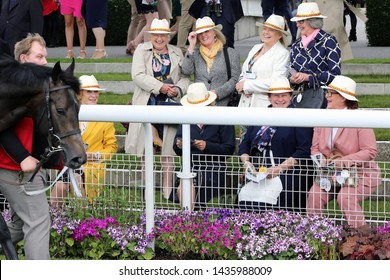 YORK RACECOURSE, NORTH YORKSHIRE, UK : 14 JUNE 2019 : A group of elegant and well dressed group of female friends all wearing trilby hats laughing as a horse passes them in the Parade Ring