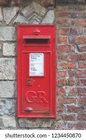 York, UK - April 2018: A red British Wall box set into a wall at York Minster, historic cathedral built in English gothic style in City of York, England, UK
