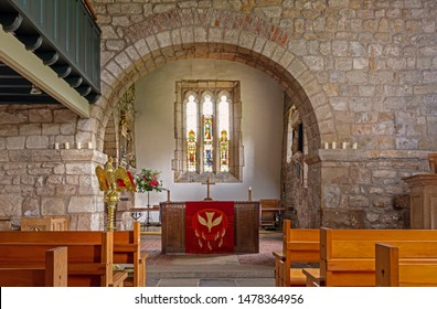 York, UK.  August 1, 2019.  Internal view of the Church of Saint Everilda in Poppleton near York.  Pews are in the foreground with an arch over the altar.  A stained-glass window is beyond.