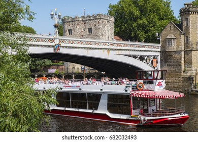 YORK, UK - JULY 18TH 2017: A City Cruises river tour boat passing underbeath Lendal Bridge in the historic city of York in England, on 18th July 2017.