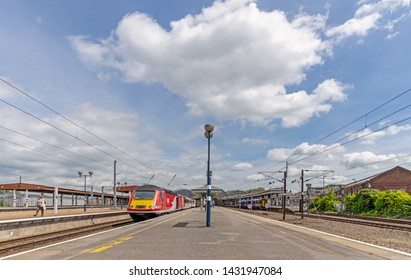 York UK. June 18, 2019. A panoramic view of York Railway station.  The platforms stretch inwards to the station and a train waits to depart.  A cloudy sky is above.