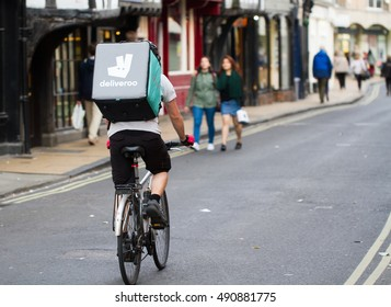 YORK, UK-SEPTEMBER 28, 2016.A cyclist from the increasingly popular take away delivery company Deliveroo speeding through city streets with a hot food delivery from take aways and restaurants to homes