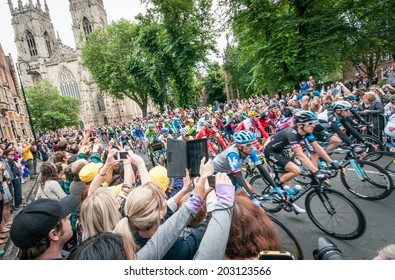YORK, UNITED KINGDOM - JULY 6, 2014: People watch the Tour de France peleton riding past York Minster in York, UK. Tour De France is one of the most prestigious cycling contests in the world.