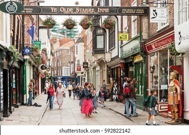 York, Yorkshire, United Kingdom - June 23, 2006: Stonegate street is one of the oldest streets in York with some of the half-timbered buildings. Tourists visiting and shopping in  Stonegate street.