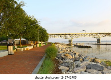 The Yorktown Riverwalk and waterfront beach area during early morning sunrise looking west towards Williamsburg through the Coleman bridge as the sun rises in the east