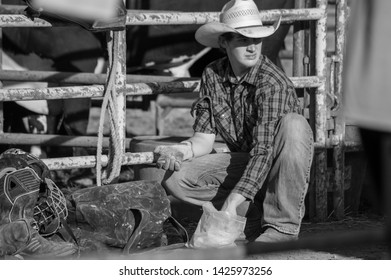 Yorkville, IL / USA - July 7, 2018: Big Hat Rodeo Kendall County Fair Cowboy Preparing Gloves and Rope with Rosin World Championship
